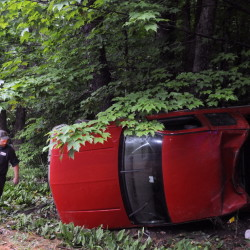 A winch is attached to a pickup that struck a tree and rolled over on Hallowell-Litchfield Road in Litchfield on Wednesday. The driver is charged with drunken driving and marijuana cultivation.