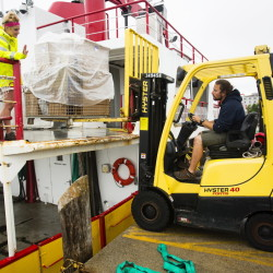 Casco Bay Lines employees Amanda Douglas and Isaac Wipfler load freight pallets onto a ferry in Portland on Wednesday. The ferry operator is now running on its peak summer schedule, and Maine's transportation officials expected record crowds over the Fourth of July weekend. The balmy weather forecast helped draw visitors during what is the traditional kick-off of the summer tourist season.  Carl D. Walsh/Staff Photographer