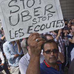 "A striking taxi driver holds a placard reading ""Stop Uber, Stop listening,"" referring to the latest U.S. spying report in France, during a taxi driver demonstration in Paris on June 25."