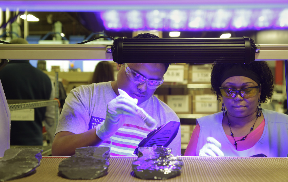 Under ultraviolet light, workers assemble the New Balance 950v2 sneaker in the company's plant in Boston. A year after the commitment was made, New Balance is pressing the Pentagon to buy American-made footwear for the troops.