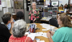 """Joan Gordon, center, executive director of the Biddeford Free Clinic, helps volunteers fill out paperwork for clients to get health insurance. """"I know it's time to go, but it's hard,"""" she admits."""