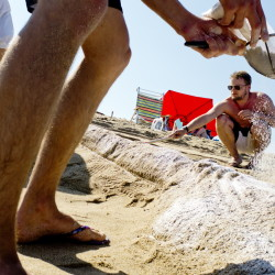 Josh Wilson of Montreal, foreground, spreads confectioner's sugar on a sculpture of the Statue of Liberty as Ben Mortley of Australia works on the crown during the sand sculpture competition Friday.