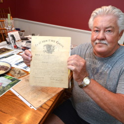 Ed Isaacs holds the July 1865 Civil War discharge papers of  his great-grandfather Edwin L. Tuttle in Norwalk, Conn. The (Norwalk) Hour