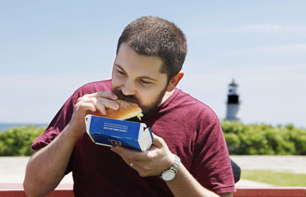 Matt Smith samples a McDonald's lobster roll Thursday at Fort Williams Park in Cape Elizabeth.  Joel Page/Staff Photographer