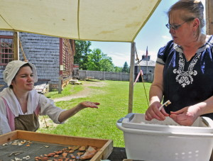 Historic interpreter Julia Pierce shows an artifact she has just cleaned to director Linda Novak at Old Fort Western in Augusta.