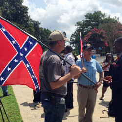 Randy Saxon, left and Wayne Whitfield, both of Anderson, S.C., discuss the Confederate flag on the South Carolina Statehouse grounds with Brodrick S. Hall of Atlanta, right, on Monday.