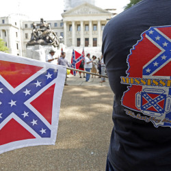 A member of the Sons of Confederate Veterans waves a small Confederate battle flag as he waits for a Save the Flag rally to begin on the steps of the Capitol in Jackson, Miss., on Monday. About 40 people participated in the demonstration.