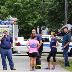 Emergency personnel stand outside a campground surrounded by police tape near Moncks Corner, S.C., on Tuesday, after an F-16 fighter jet smashed into a small plane over South Carolina.