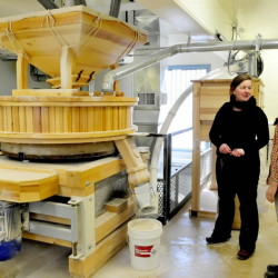 Somerset Grist Mill owner Amber Lambke, left, and head miller Julie Zavage discuss an order being ground in the stone mill, far left. Lambke said the kosher certification is just one part of the healthy food production at the mill.