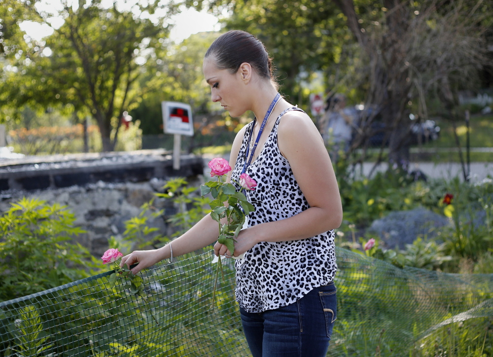 PORTLAND, ME - JULY 10: Ashley Summers, the wife of Steven Summers, one of the six victims who died in a fire in Portland on Nov. 1, 2014, lays flowers at the site of the fire on Noyes Street in Portland. The landlord of the building, Gregory Nisbet, was indicted on 6 counts of manslaughter on Friday, one for each of the victims of the state's deadliest fire in decades. (Photo by Derek Davis/Staff Photographer)