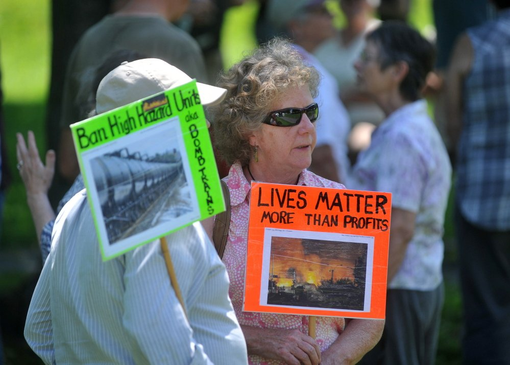 Activists carry signs opposing the transport of flammable crude oil by rail.