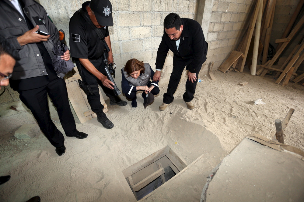 Mexico's Attorney General Arely Gomez Gonzalez, second from right, looks into the entrance of a tunnel connected to the Altiplano Federal Penitentiary. The ventilated tunnel was allegedly used by drug lord Joaquin 'El Chapo' Guzman to escape the prison.