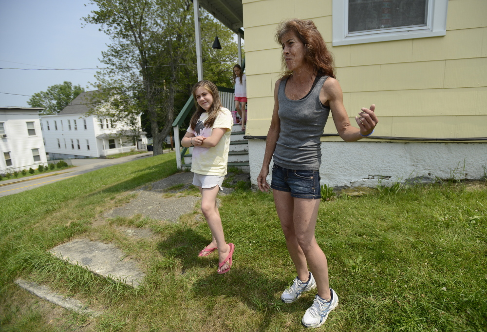 """Kristine Sampson, who lives at the corner of Clifford and George streets in Biddeford, across the street from where Sunday's """"swatting"""" incident happened, describes on Monday what she saw. With her is her daughter Skyler Verrill, 11, and visible to the left of Verrill is the apartment building at 41 Clifford St."""