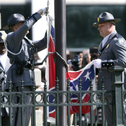 An honor guard from the South Carolina Highway Patrol lowers the Confederate battle flag as it is removed Friday from the Capitol grounds in Columbia, S.C. Legions of people clapped, cheered and cried as the flag came down.