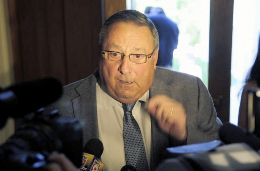 Gov. Paul LePage talks to a reporter about his veto messages as he leaves the State House on July 16. He indicated in interviews before the Supreme Judicial Court ruling that he will not enforce the 65 laws and would seek additional relief in court to block their implementation.  Joe Phelan/Kennebec Journal