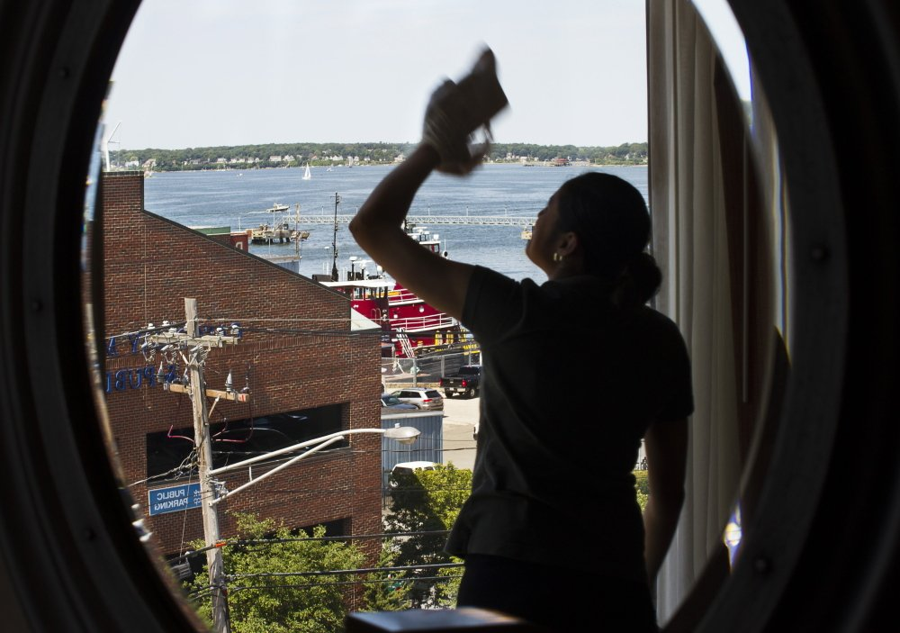 With the tall ships festival and other summer events going on this weekend, Hilton Garden Inn housekeeper Karen Gomez makes sure there's a clear view of Casco Bay from a window Thursday.