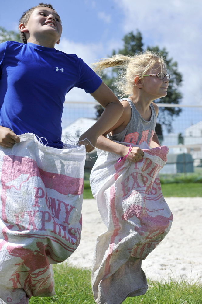 Zane Ford, 10, left, battles Kendyl Ashcom, 5, to the finish line in a sack race at a Youth Fair in Johnstown, Pa., on Tuesday. The Youth Fair is held to raise awareness about the dangers of drugs and is sponsored by Cambria County's court system.