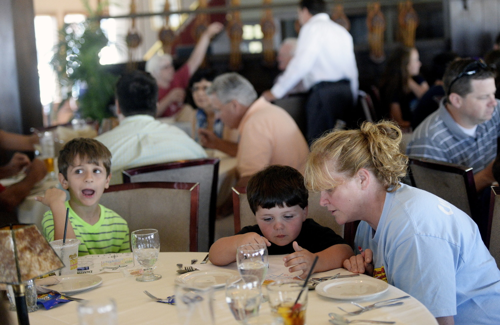 Laurie Joseph colors with her son Wyatt Holan, 4, sitting next to Joel Lamorte, 6, as the visitors from Pennsylvania wait for dinner Monday at DiMillo's. Joseph said keeping kids busy at restaurants doesn't always work, but staff should not yell at them.