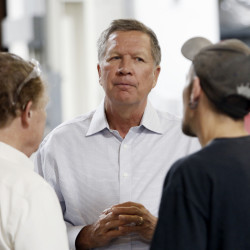 In this July 13, 2015, file photo, Ohio Gov. John Kasich talks with Joshua Bowman, right, and Joe Shean during a visit at RP Abrasives in Rochester, N.H.