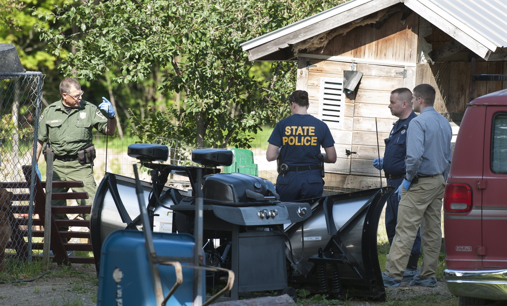 State police and a game warden talk Friday near the scene of a suspicious barn fire in Benedicta. The fire may have been set by Anthony Lord, who went on a rampage later Friday.
