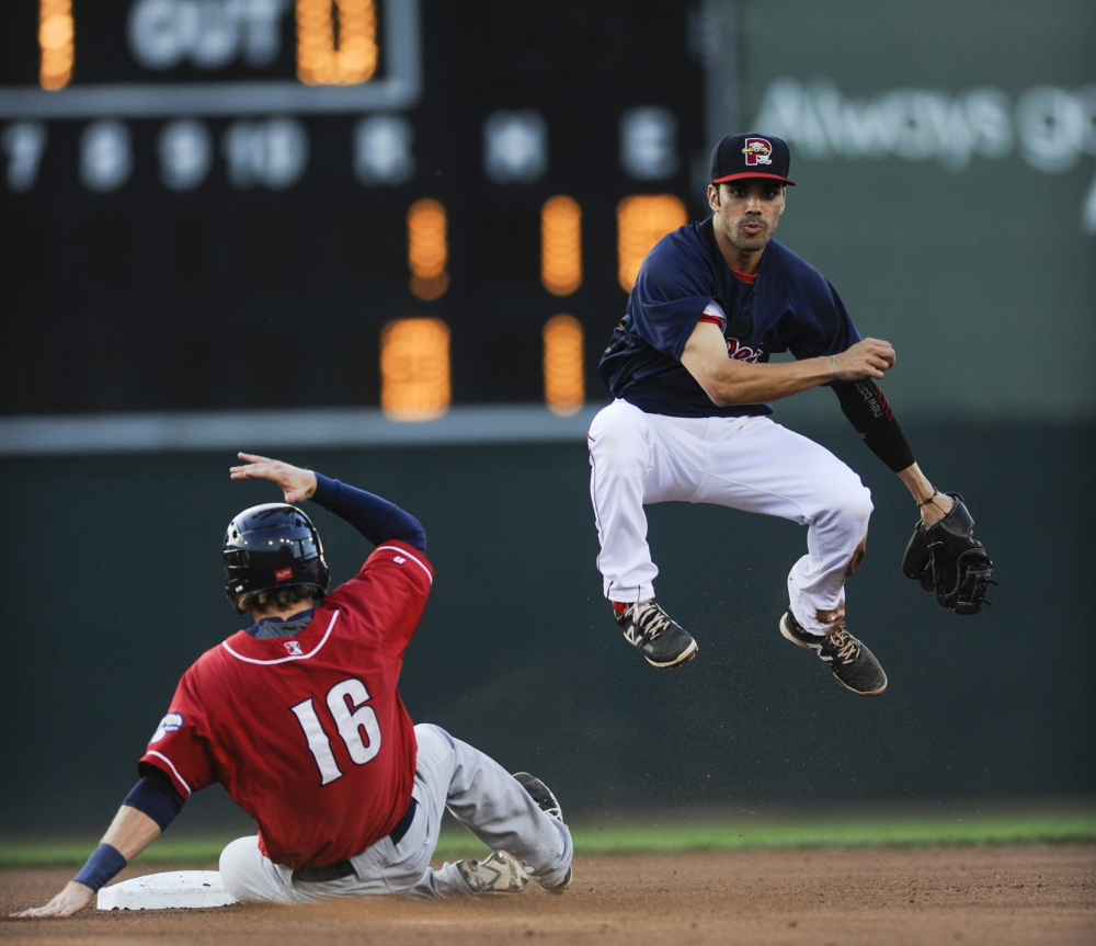 Sea Dogs second baseman Carlos Asuaje leaps to throw the ball to first base for a double play after tagging out New Hampshire's Shane Opitz on Thursday at Hadlock Field.