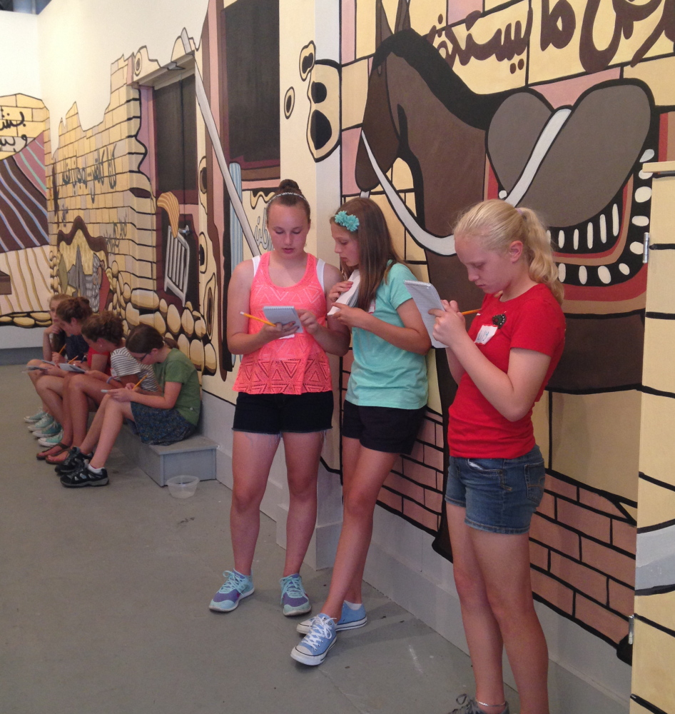 """Students in The Telling Room summer camp on review writing work on their critiques of """"We Are Staying,"""" a mural by Alina Gallo that was displayed at SPACE Gallery in Portland."""