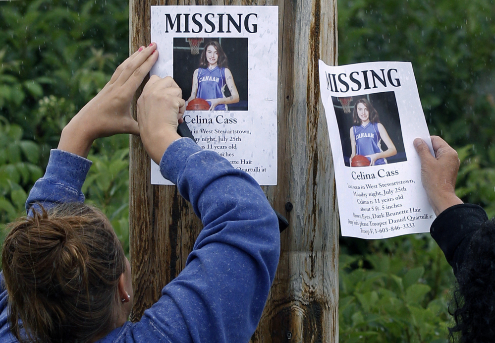 Kaylin Pettit of Stewartstown, N.H., left, and Lori McKearney of Lancaster, N.H., tack missing posters for Celina Cass to a utility pole in Colebrook, N.H., in 2011.