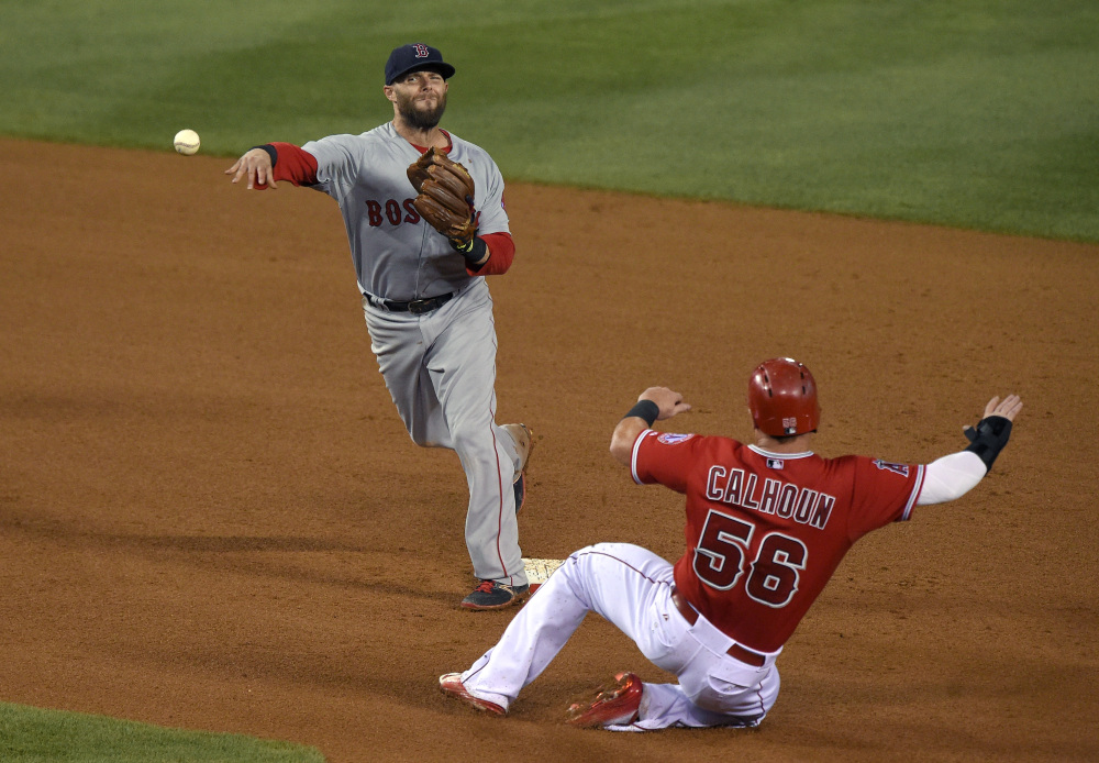 Boston Red Sox second baseman Dustin Pedroia, left, completes a double play against the Los Angeles Angels on July 18. Pedroia was placed on the disabled list Saturday.