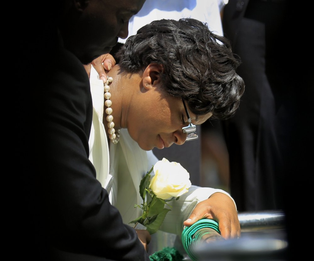 Sandra Bland's sister Sharon Cooper kneels at Bland's burial site at the Mt. Glenwood Memorial Gardens West cemetery Saturday in Willow Springs, Ill.