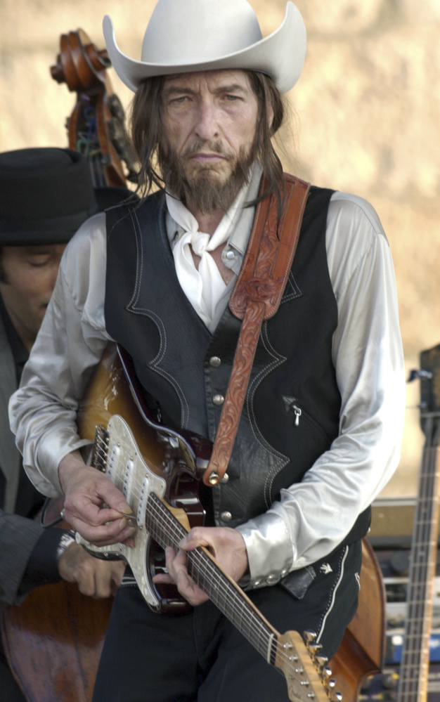 Bob Dylan plays an electric guitar at the Newport Folk Festival in 2002. The 1965 festival marked the first time he went electric publicly.