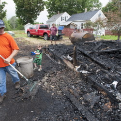 Aided by his grandson Joshua, Rick Irish rakes embers near the charred remains of the family's cow barn in the Aroostook County town of Benedicta. The Irishes told police they were convinced Anthony Lord had set the July 16 fire; Lord was charged with murder and kidnapping after a rampage the next day.