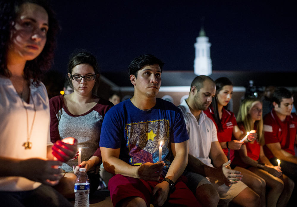 "Students gather during a vigil Friday night for The Grand 16 theater shooting victims at the University of Louisiana at Lafayette. John Russell Houser stood up about 20 minutes into Thursday night's showing of the film ""Trainwreck"" and fired on the audience with a semi-automatic handgun."