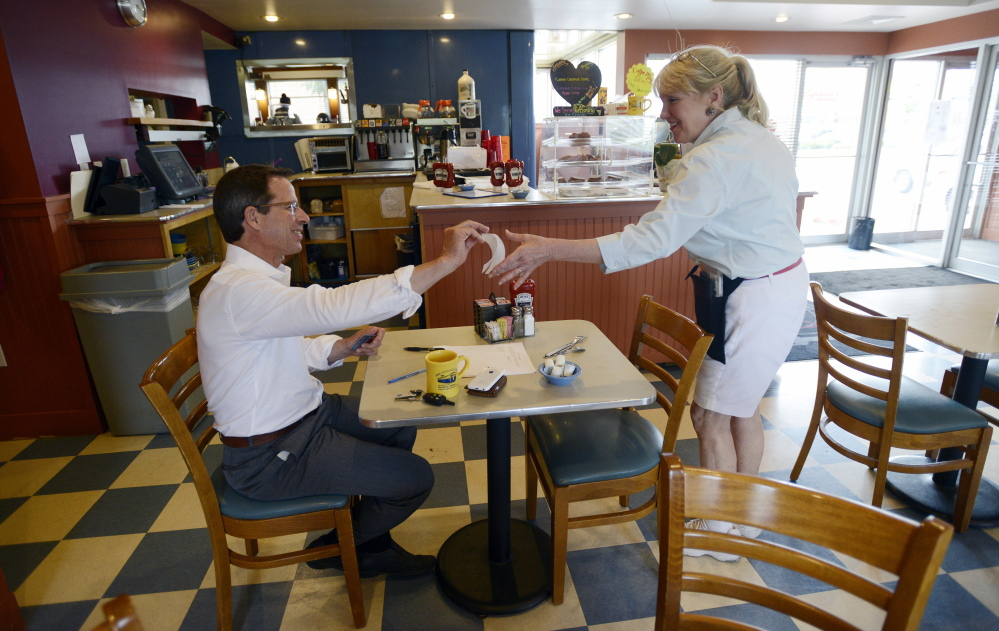 """Susie Kiehn-Geary, manager and chief server at the Miss Portland Diner, accepts the signed check from attorney Kaighn Smith of Portland on Thursday. Smith, who used to wait tables himself, said restaurant workers """"deserve every penny that they earn."""" The customer left a $5 tip on his $9.99 bill."""