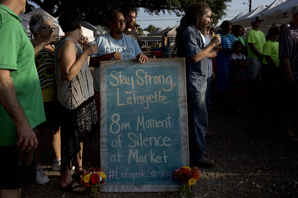 A crowd gathers around a sign for a moment of silence at a local farmers market for the victims of  a deadly shooting at the Grand 16 theatre, Saturday in Lafayette, La.