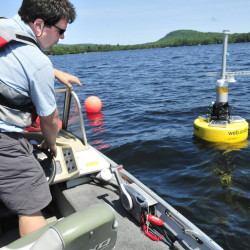 Colby College professor Whitney King approaches a buoy with electronic devices that measure a variety of water quality tests on Great Pond in Belgrade on Thursday.