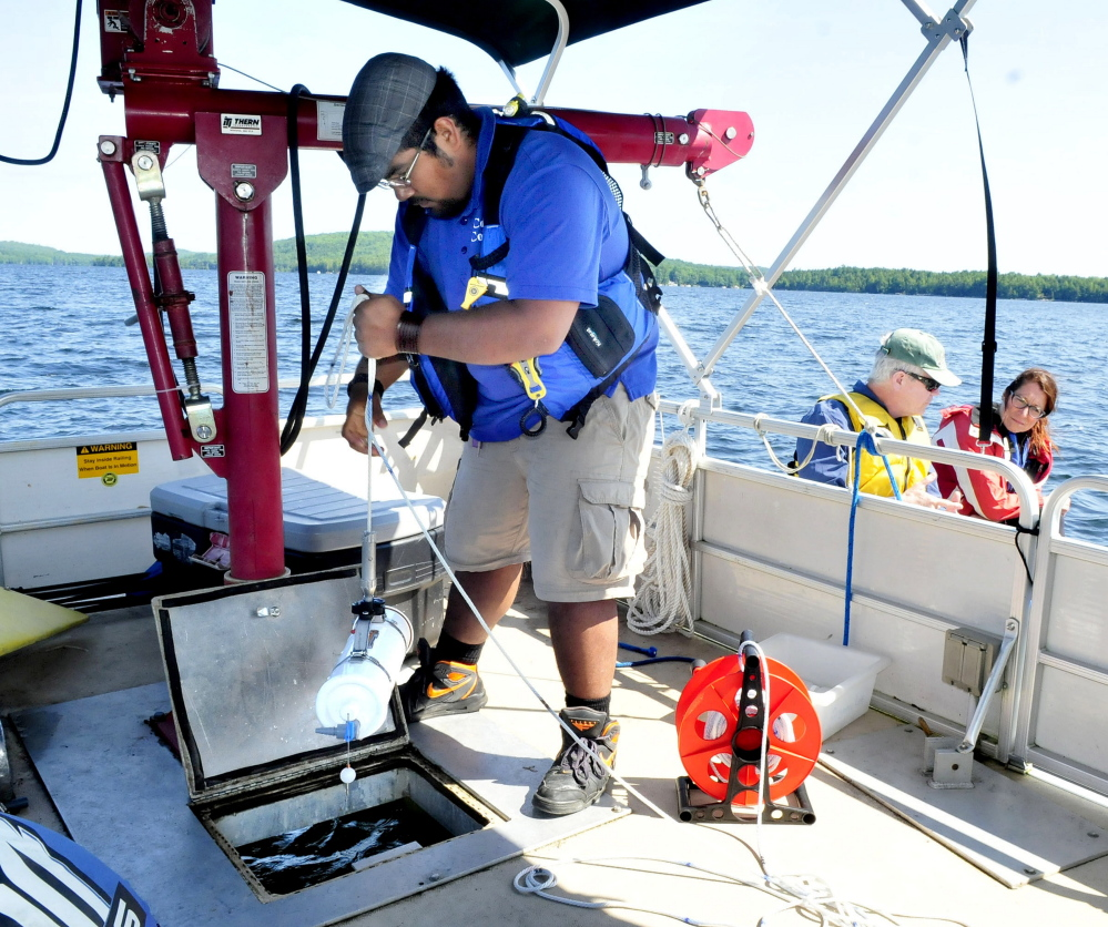 Sergio Madrigal, center, a Colby college student, lowers equipment that collects water samples at desired depths in Great Pond in Belgrade on Thursday. Charlie Baeder, executive director of Belgrade Regional Conservation Association, and Lake Science Manager Brenda Fekete wait in another boat beside the research vessel.
