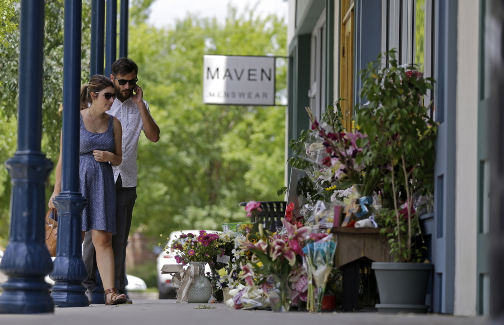 """David and Sarah Flores, both of Lafayette, view flowers placed outside the Red Arrow Workshop on Sunday in Lafayette, La.. The store was owned by Jillian Johnson, who died when John Russell Houser stood up during Thursday night's showing of """"Trainwreck"""" and fired on the audience with a semi-automatic handgun."""
