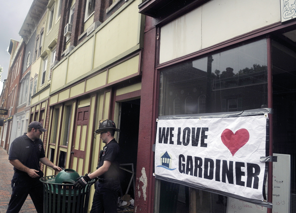 Gardiner firefighters replace a trash can last week after searching for tools lost in the July 16 blaze that heavily damaged the downtown building. Community support for businesses ruined and individuals left homeless has been unwavering.