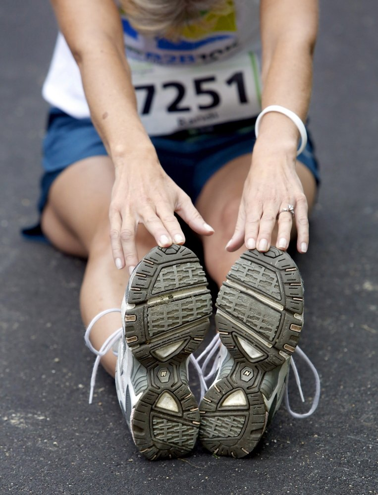 Randi Sheehan of South Portland stretches last August before the start of the Beach to Beacon 10K road race. Even though median finish times are rising steadily, race winners have broken course records four times in the past six years.