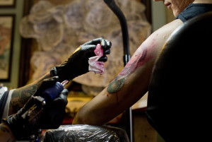 Cyndi Lou, a tattoo artist at Tsunami Tattoo in Portland, wipes away excess color while tattooing Kacie Piscatelli of Portland.