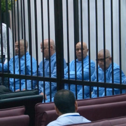 In this image made from AP video, former Libyan officials who served during Moammar Gadhafi's era sit in the defendants' cage during their trial for crimes committed during Libya's 2011 uprising, in a courtroom in Tripoli, Libya, Tuesday.