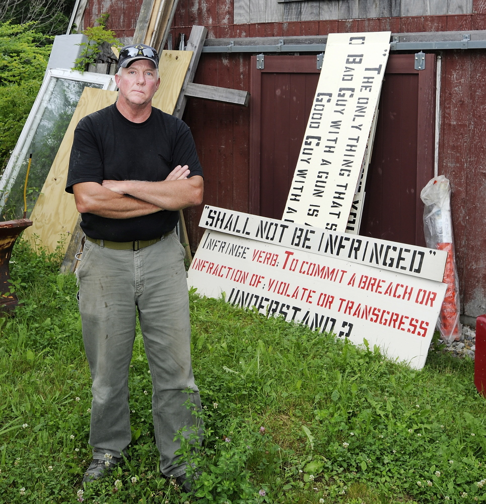 "Linc Sample of Boothbay Harbor stands Tuesday with the next sign he plans to post in his yard. He says ""half the people in town really don't like my signs and don't like me because of them."""