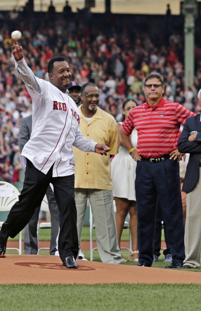 Pedro Martinez throws out the ceremonial first pitch before Tuesday night's game as former Red Sox greats Jim Rice, center, and Carlton Fisk watch. The Associated Press