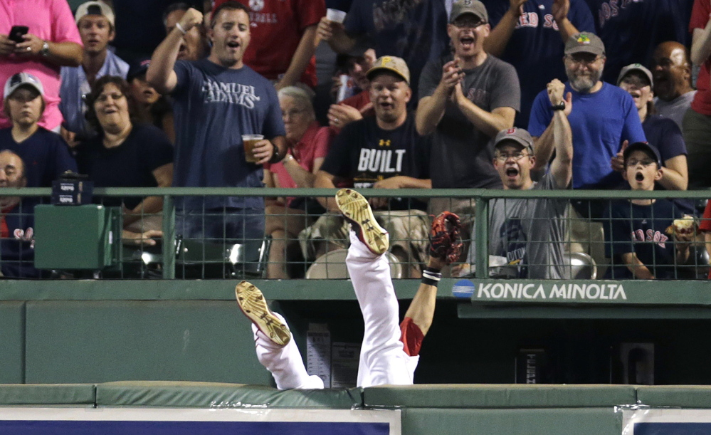 Boston Red Sox center fielder Mookie Betts flips over the bullpen wall while trying to field a drive by Chicago White Sox's Jose Abreu during the sixth inning Tuesday at Fenway Park in Boston. Betts dropped the ball when he landed and umpires ruled the play a home run after video replay review.