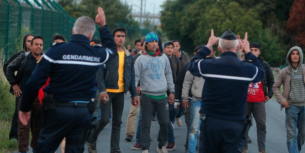 Following British complaints of lax security, French police block migrants from train tracks leading to the Channel Tunnel that connects France and Britain.