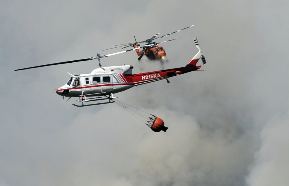 With wildfires raging this summer in drought-stricken California, two firefighting helicopters pass near each other over Willow Creek Canyon near Bass Lake in the central part of the state on Monday.
