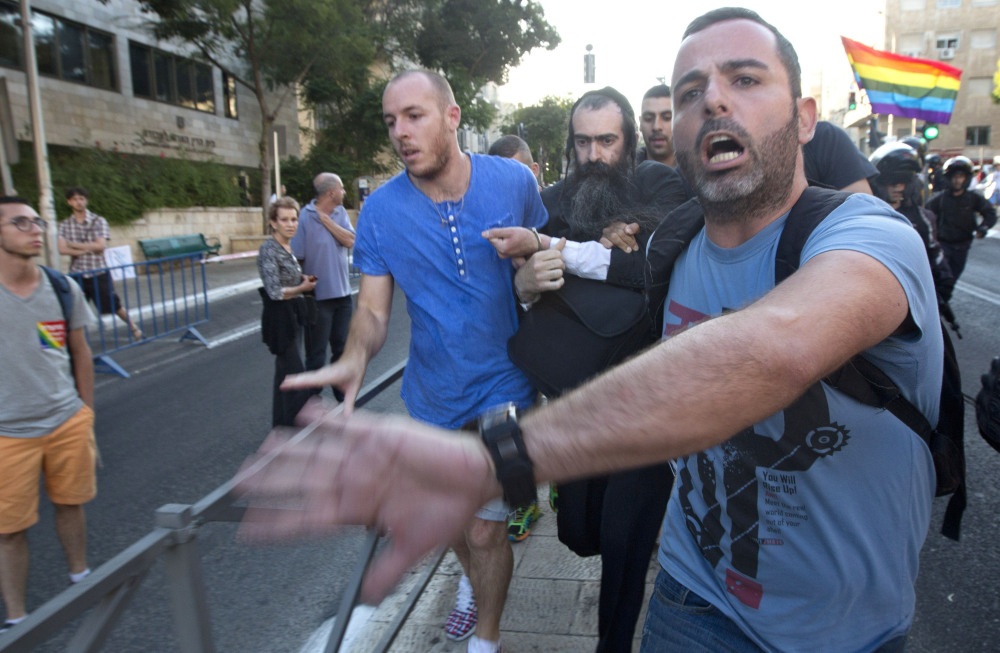 Plainclothes Israeli police detain a man after he attacked people with a knife during a gay pride parade on Thursday in central Jerusalem.
