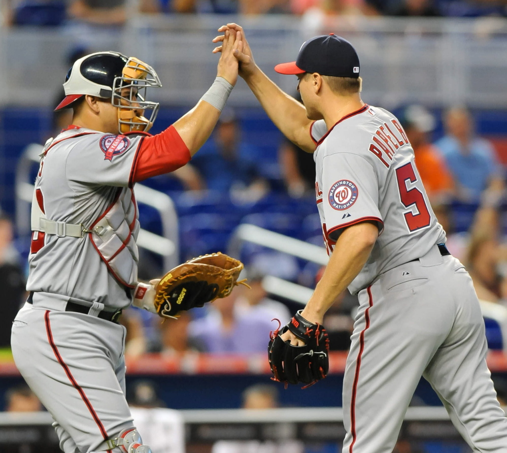 Jonathan Papelbon high-fives catcher Wilson Ramos on Thursday after recording his first save with the Washington Nationals.