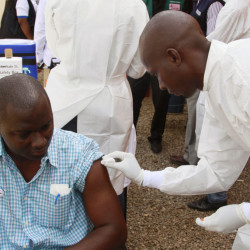 A health worker cleans a man's arm before injecting him with a Ebola vaccine in Conakry, Guinea. The outbreak has killed 11,000 in Africa.