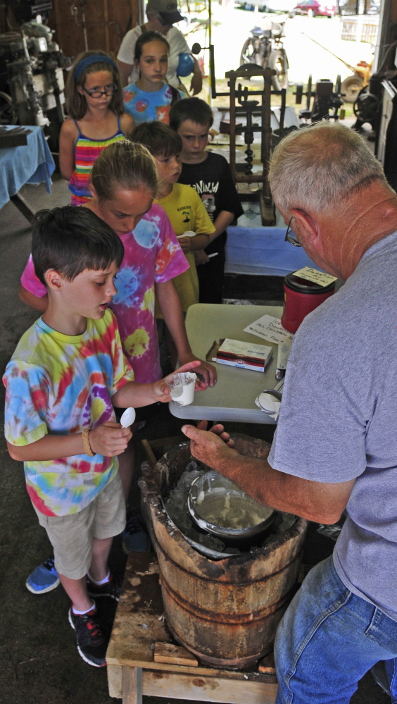 """Gary Buzzell of Greene serves the freshly made ice cream. He said he can tell when the batch is ready by taking a turn on the crank. """"When it gets so I can barely turn it, it's pretty well done,"""" he said."""